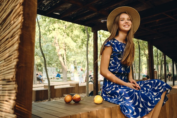 A young beautiful smiling Ukrainian woman in a blue dress and a hat joyfully sitting with peaches