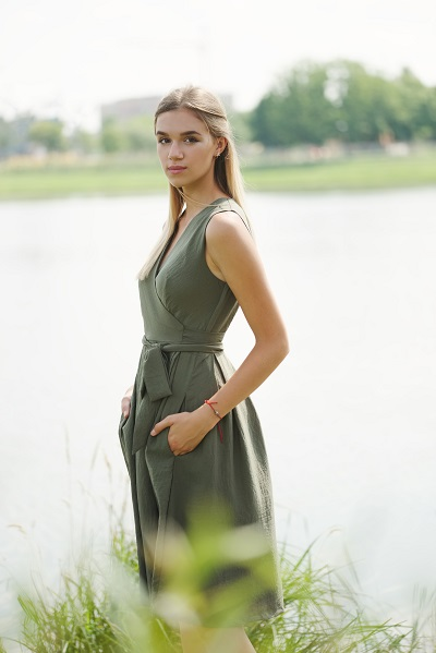 Portrait of beautiful young Ukrainian woman standing near a nice pound outdoors