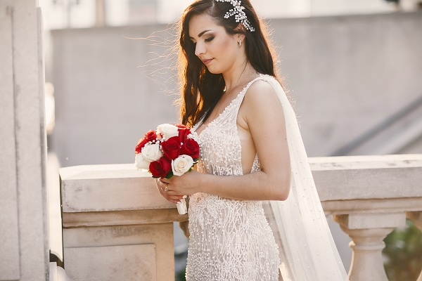 Elegant Ukrainian bride with a perfect bouquet of flowers standing in the city