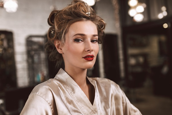 Close up young pretty Ukrainian lady with wavy hairstyle and red lips watching at the camera