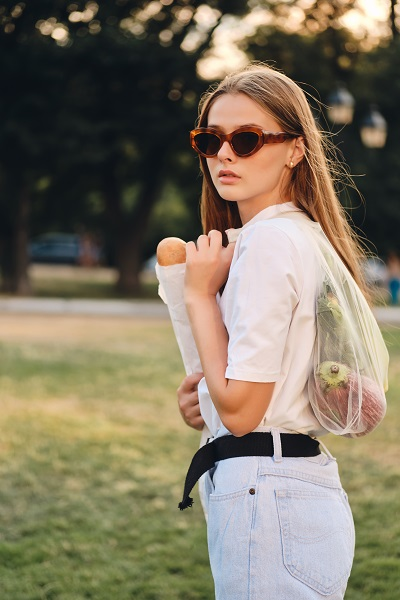 Stylish Ukrainian girl in sunglasses holding her baguette bread and vegetables in an eco-bag