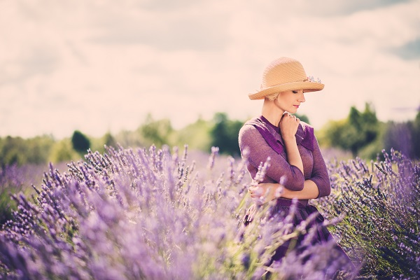 Enigmatic Ukrainian woman in a purple dress and hat in a lavender field