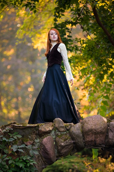 Red-haired Ukrainian woman wearing a Victorian outfit posing in the deep forest