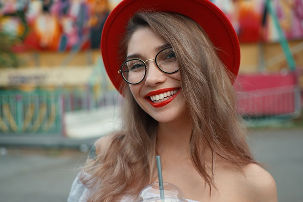Cheerful young Ukrainian woman holding a drink while smiling and posing for the camera