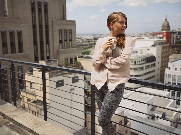 Attractive Ukrainian woman drinking coffee and enjoying the city view from her balcony