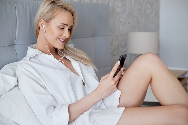 Relaxed smiling Ukrainian blond woman lying in a white bed and using a smartphone