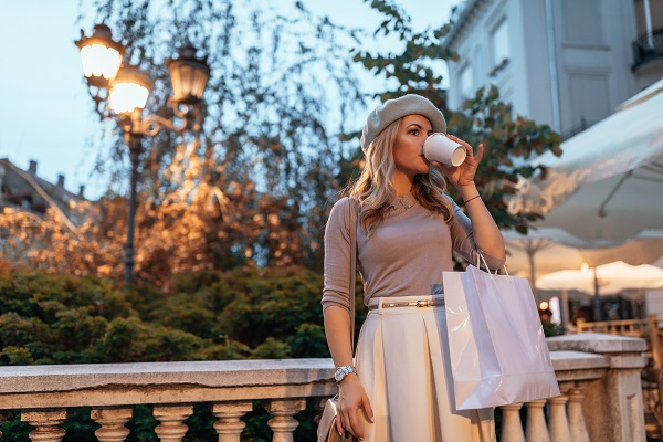 Wonderful curvy attractive Ukrainian lady drinking her cup of coffee while holding a shopping bag