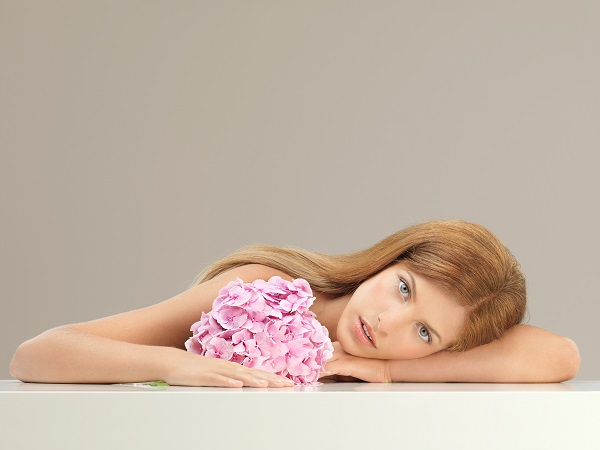 Beautiful charming young Ukrainian woman with a small bouquet of pink flower dreamily looking in the camera